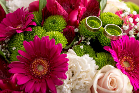 two object: Close up on beautiful wedding bouquet of pink, green and white flowers with pair of rings on top. Stock Photo