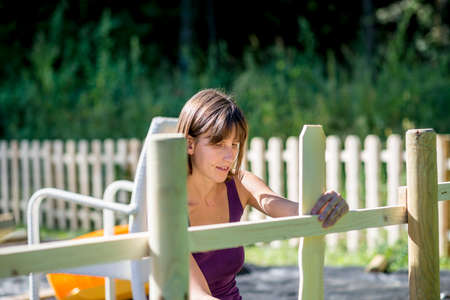 wooden fence: Young adult woman preparing fence to be painted or stained outdoors in natural area.