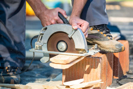 Close up on unidentifiable hands using circular saw to cut planks of wood outdoors.