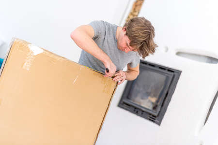 short sleeved: Single young adult man in gray short sleeved shirt cutting open a large brown box with blade. Stock Photo