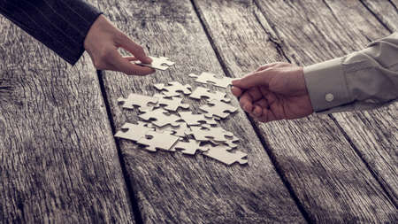 business puzzle: Two different hands of unidentifiable business people reaching for puzzle pieces from stack.