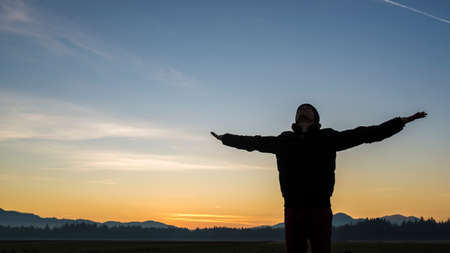stretched: Young person celebrating the sunrise or sunset standing with outstretched arms silhouetted against a colorful orange sky.