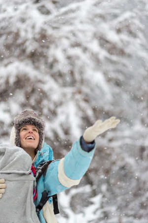 warmly: Warmly dressed happy woman holding her hand out to the winter snow during a fresh snowfall as she enjoys a walk in a snow covered forest. Stock Photo