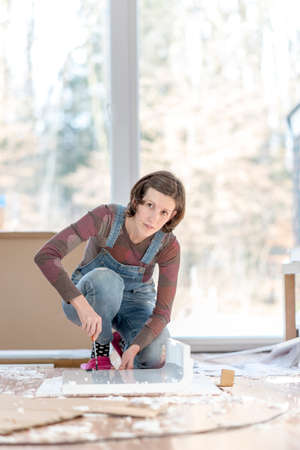 old furniture: Single young adult woman in overalls working on floor with old furniture or projects in home.