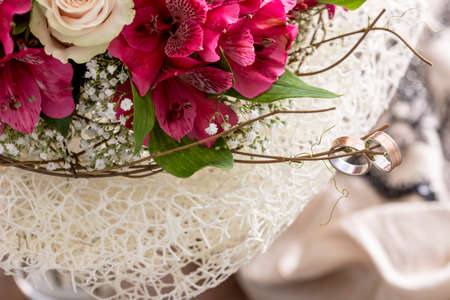 close up on pair of rings on branch of bouquet with pink flowers