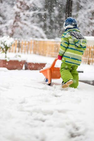 Young child dressed in a warm green outfit walking away from the camera pushing a wheelbarrow through snow in a winter garden landscape. Stock Photo
