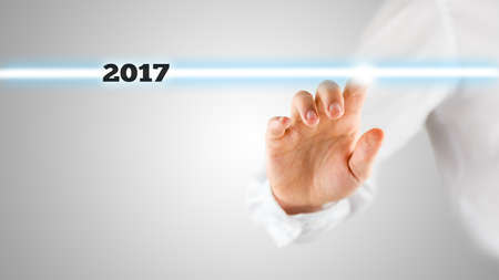 Finger of unidentifiable business man in white shirt touching glowing blue line with year 2017 text.