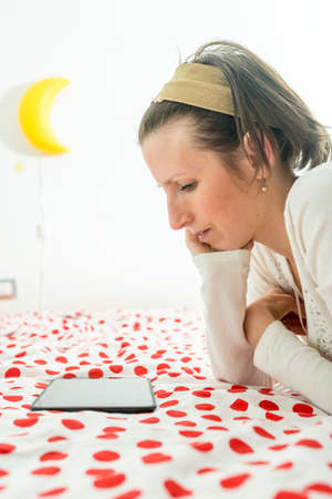 alice band: Woman wearing an alice band in her hair lying looking on digital tablet on her bed.
