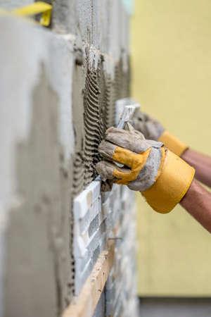 scored: Gloved hands of worker installing ceramic wall tiles over freshly scored mortar compound.