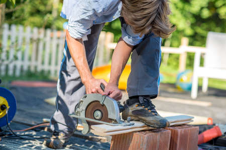 Unidentifiable single man with rolled up sleeves cutting boards with a circular saw outdoors.