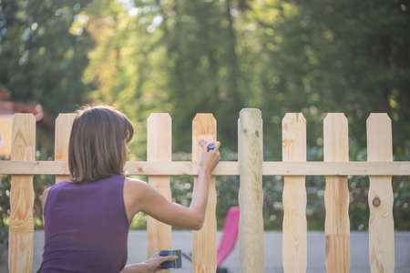 picket: Woman varnishing a wooden picket fence outdoors in her garden in summer, retro faded effect with copy space. Stock Photo