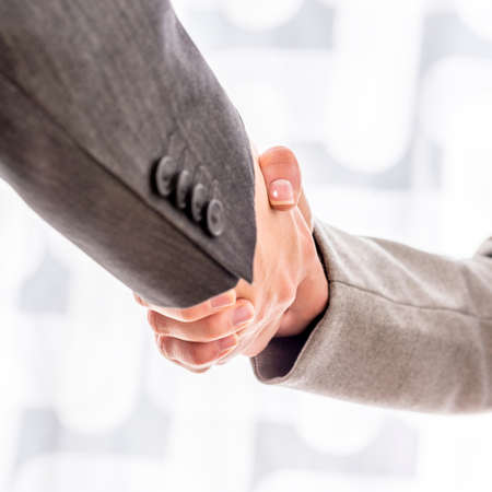 Business man and woman in formal attire shaking hands on a deal over a high key background, close up oblique angle view.