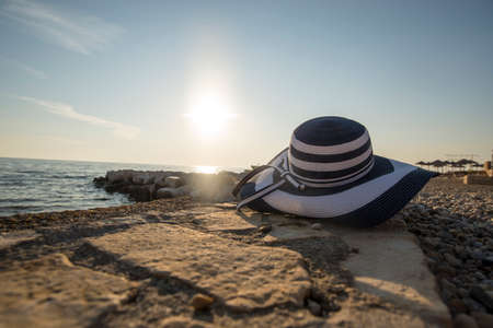 sunhat: Fashionable straw sunhat at the seaside lying on a shelf of rock overlooking the ocean with the evening or morning sun low on the horizon in the background, conceptual of a summer vacation.
