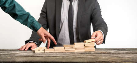 Unidentifiable businessmen stacking various flat wooden blocks for the other one to walk his fingers up towards career growth. Stock Photo