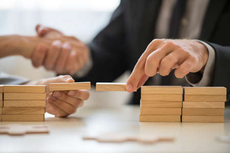 Teamwork or building bridges concept with a businessman and woman holding wooden building blocks to form a bridge over a gap while clasping hands in the background. Archivio Fotografico