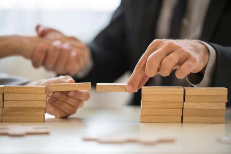 Teamwork of gebouw overbrugt concept met een zakenman en een vrouw die houten bouwstenen om een brug over een kloof te vormen terwijl omklemde handen in de achtergrond.