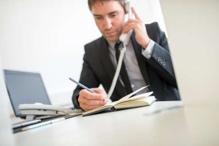 scheduling: Businessman making a note in his diary as he talks on a telephone in the office scheduling an appointment.