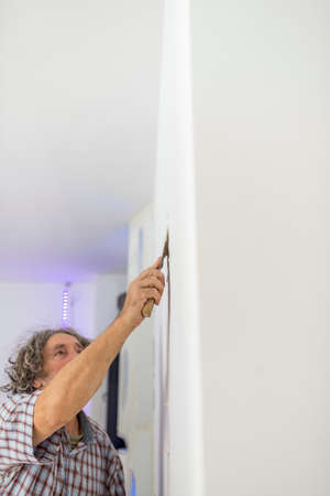 newly: Decorator retouching imperfections in a newly painted clean white wall with a small spatula in a DIY or renovations concept. Stock Photo