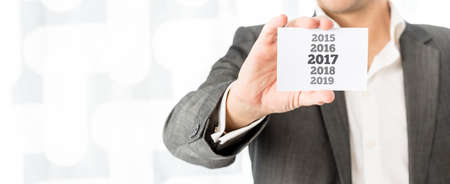 space for type: Businessman celebrating the 2017 New Year holding up a business card with year dates 2015 through 2019 with the date for 2017 in bold type, copy space alongside.