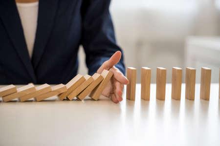 책임을지는 것에 대 한 개념에 대 한 테이블에 떨어지는 블록을 중지하는 비즈니스 여자의 손에보기를 닫습니다. 스톡 콘텐츠