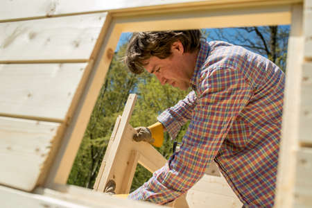 Carpenter or DIY homeowner building a wooden hut outdoors in the garden fitting the window and door frames viewed through a window opening. Stock Photo