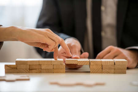 teamwork concept: Business teamwork and cooperation concept -  male hand supporting a bridge made of wooden pegs for a female hand to walk its fingers across towards promotion and progress.
