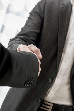 pacto: Cierre de vista de los brazos de dos hombres de negocios en trajes de darle la mano conceptuales de un acuerdo o convenio. Foto de archivo