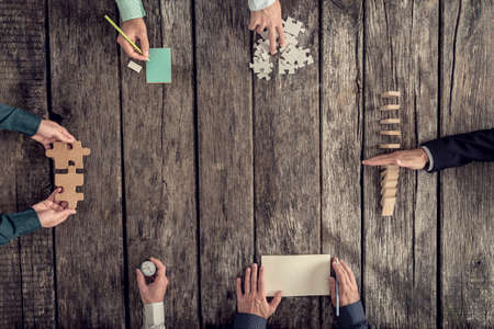 Business strategy and brainstorming concept with a team of six businessmen holding puzzle pieces, writing down ideas on paper and stopping domino effect, top view. Archivio Fotografico