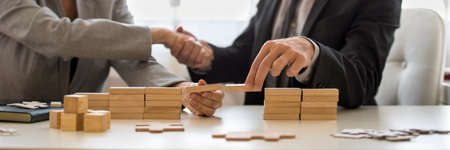 Businessman and businesswoman holding wooden building blocks to form a bridge over a gap while shaking hands.