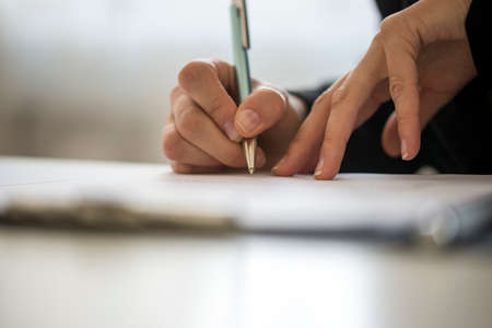 person writing: Hands of a person writing on a notepad on a table with copy space. Stock Photo