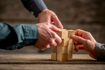 Hands of three people building a tower of wood blocks on a table, teamwork concept. Stockfoto