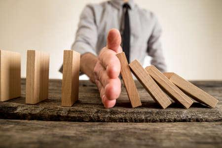 ビジネスマン イメージを間近に落ちると直立木製ブロックの間の彼の手を挿入するドミノ効果を停止します。