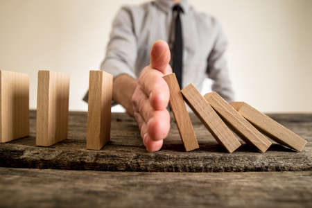 Businessman halting the domino effect inserting his hand between falling and upright wooden blocks in a close up conceptual image. Reklamní fotografie
