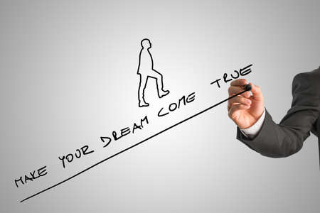 Hand of businessperson writing make your dream come true along upward trend line on whiteboard next to walking figure. Stock Photo