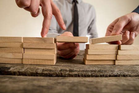 building blocks business: Businessmen solving problems by building bridges with wooden blocks to span a gap for partner to walk his fingers across in a conceptual image.