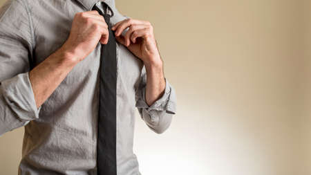 his shirt sleeves: Close-up view of man in grey shirt with rolled up sleeves adjusting his black necktie with both hands, standing against light brown background with copy space. Stock Photo