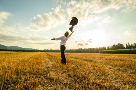 liberated: Scenic rear view of liberated businessman in field throwing jacket in air with sunshine and cloudscape background. Stock Photo