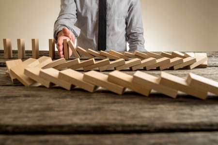 metaphor: Hand stopping domino effect of wooden blocks for concept about business and accountability.