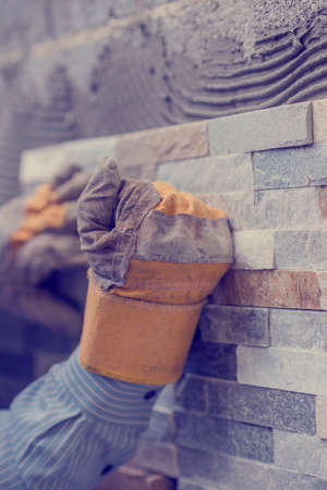 building wall: Close-up of hands of tiler worker in gloves pressing brick tiles to stick it to the wall.