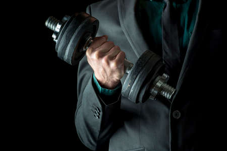 potency: Businessman in formal suit lifting weights. Concept of power and determination in business. Over black background. Stock Photo