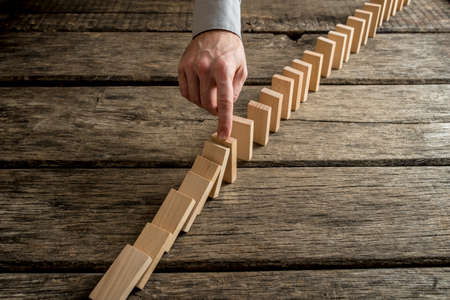 Hand stopping domino effect of wooden blocks for concept about solving problems. Imagens - 71127889