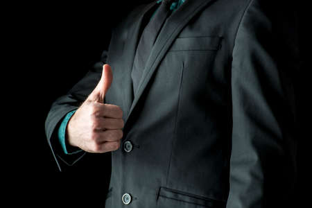 Closeup of businessman showing a thumbs up sign towards you. Over black background. Archivio Fotografico