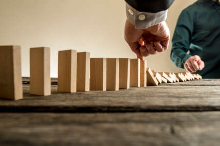 business problems: Businessman stopping the domino effect of falling wooden blocks initiated by a colleague or business competition in a concept of success and solving problems. Stock Photo