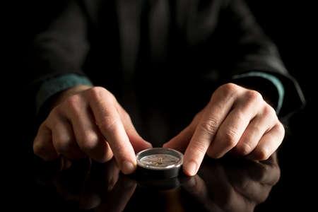 反射の黒いテーブルの上のコンパスを保持している実業家。 写真素材 - 71448218