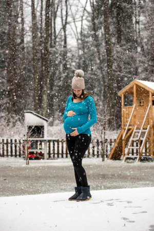 cradling: Pregnant woman holding her belly standing outside in winter hat and blue sweater under snowfall in rural area. Stock Photo