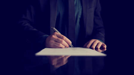 silver reflection: Retro image of businessman signing document or contract with silver pen on a black desk with reflection.