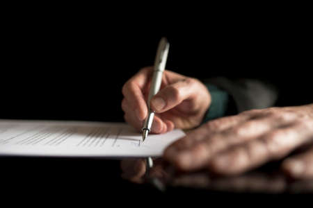 Low angle view of a male hand signing contract or subscription form with a pen on black desk.