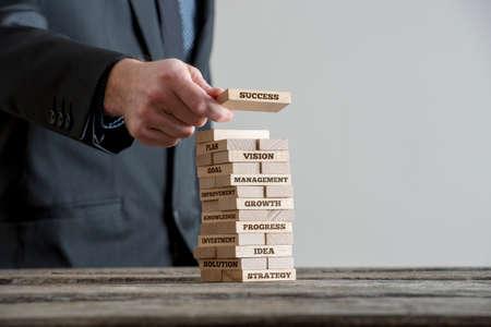 블랙 스위트 건물에서 사업가 동기 부여 비즈니스 개념 나무 도미노 벽돌 타워 타워 건물 전략에 대 한 표지판입니다. 회색 벽 복사본 공간이 나무 테