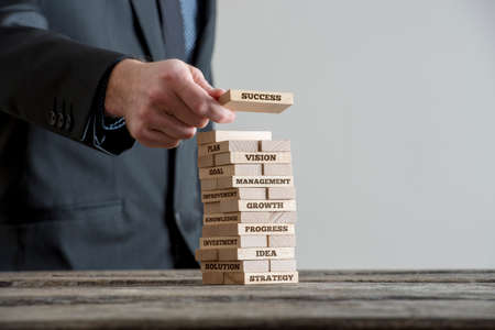 Businessman in black suite building tower of wooden domino bricks with motivational business concept signs about company building strategy. Close-up on wooden table with grey wall copy space.