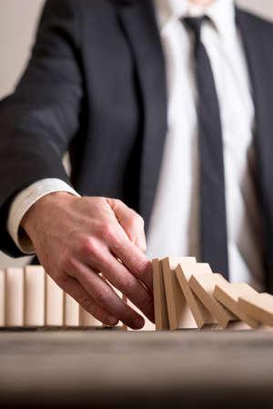 Verticale close-up van zakenman dragen pak onderbreken domino-effect door het stoppen van houten domino stenen uit afbrokkelende met zijn hand. Stockfoto